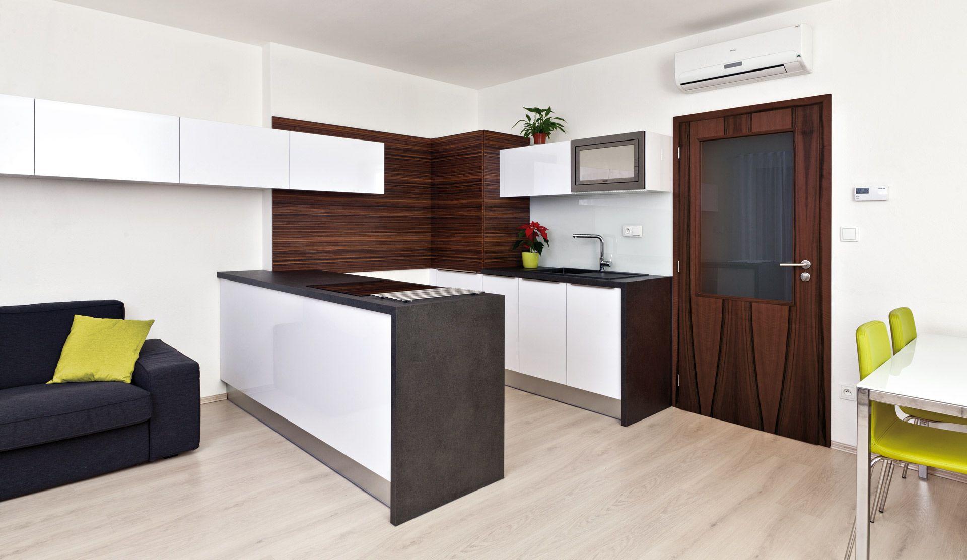 Cílem bylo získat více pracovní plochy v kuchyni a opticky oddělit obývací část prostoru.