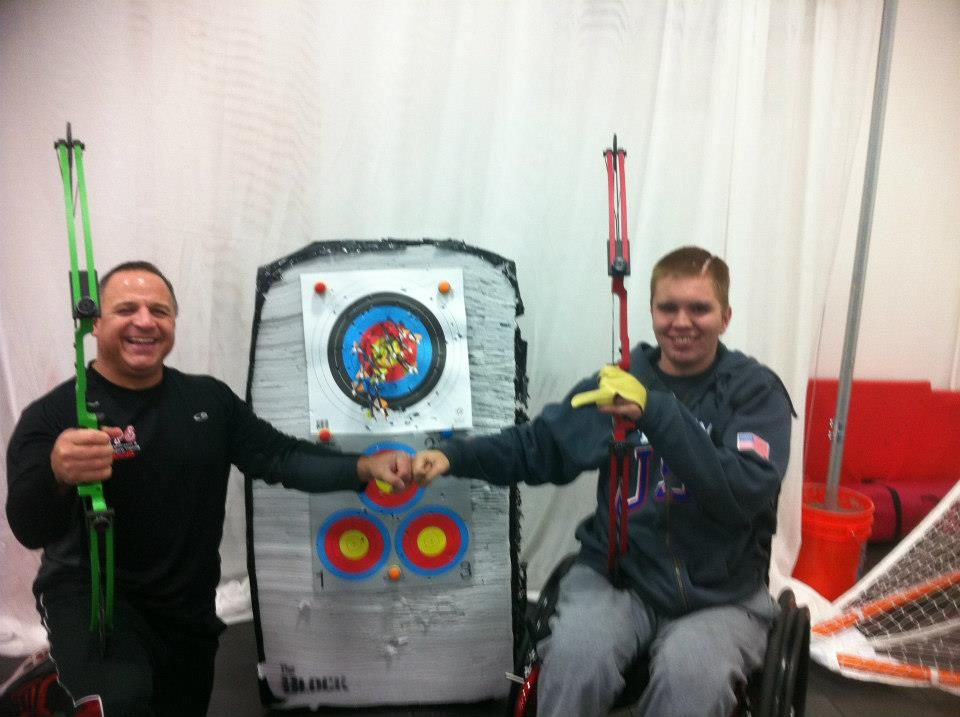 Coach Ron and Brian training with compound bows.