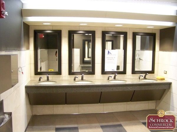 traditional commercial restroom with framed mirrors