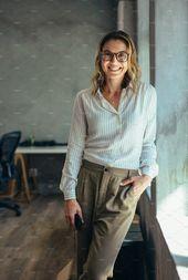Photo of Positive Geschäftsfrau, die im Amt steht. Frau in lässig am Fenster stehend …