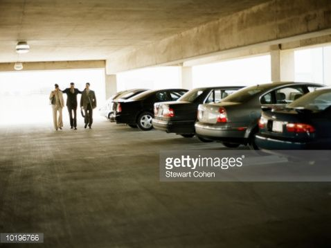 Stock-Foto : Three business people walking together in parking lot