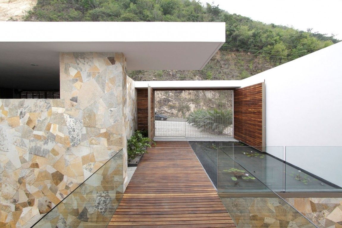 House design gate - Beautiful Coastal House Design With White Modern Gate And Natural Stone Wall Featuring Wooden Floor Entry