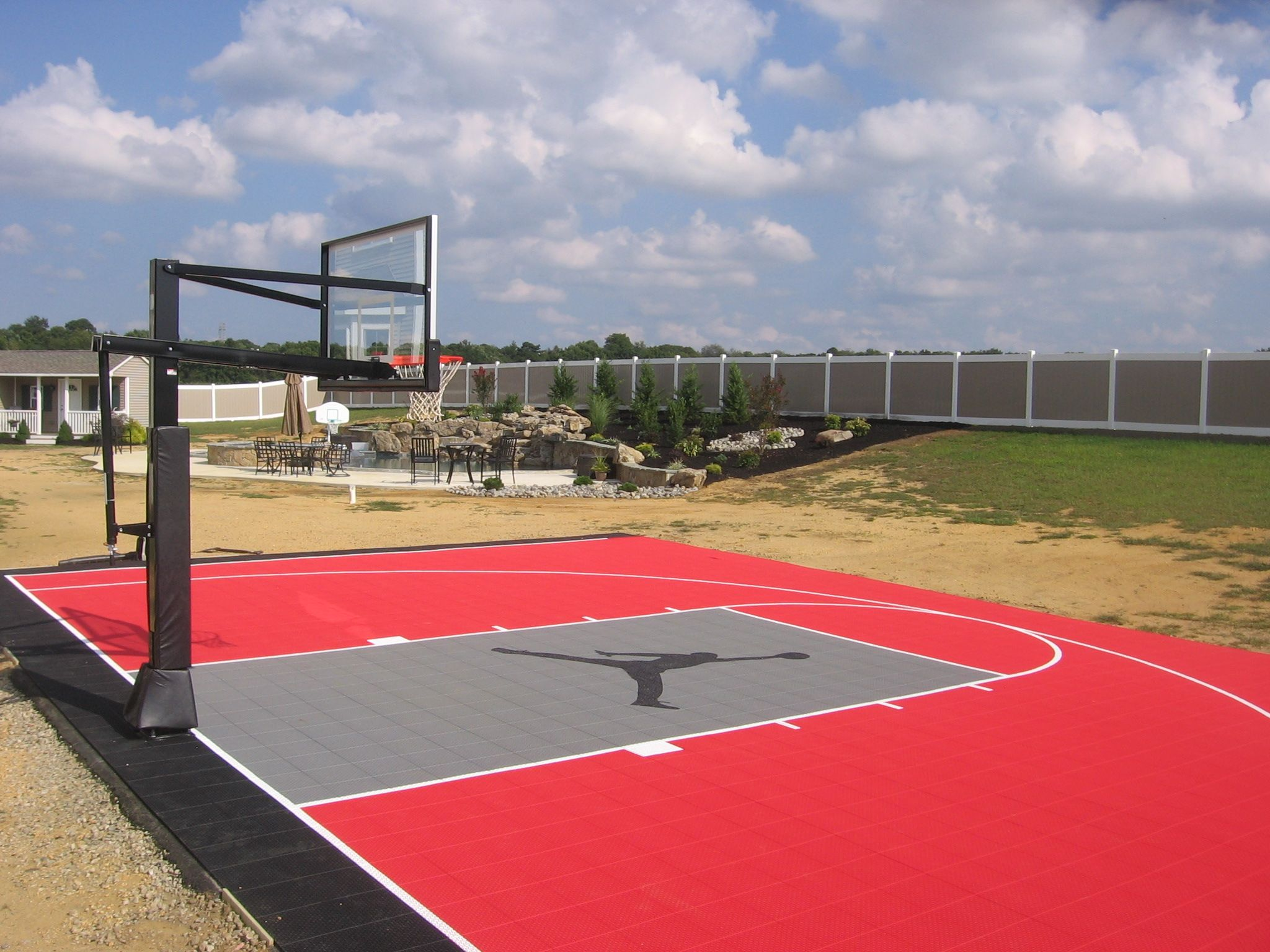 backyard half basketball court with custom logo built by deshayes