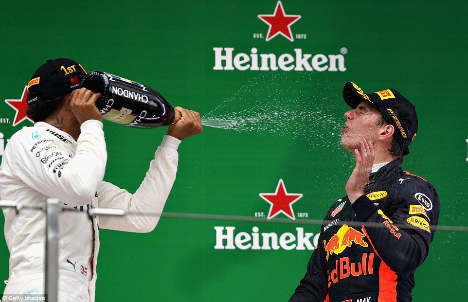 Chinese Grand Prix winner Hamilton sprays champagne on Max Verstappen, who secured an impr...