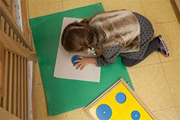 At  Metropolitan Montessori School, a child uses metal insets to learn about the circle.