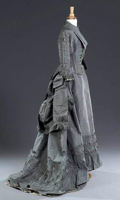 Gray silk taffeta afternoon dress, ca. 1875. Bodice has ruched sleeves and tailing ribbons at back; skirt has ruched tiers and ruched and pleated bustle. Live Auctioneers