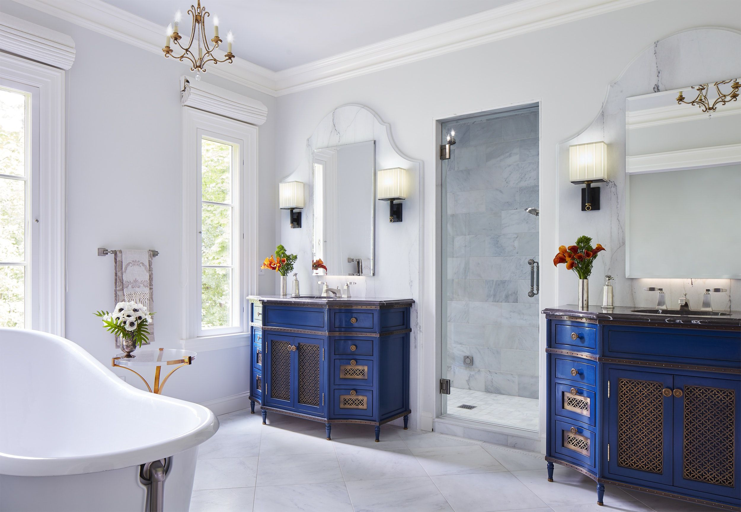 Twin vanities set on profiled marble wall frames which flank a ...