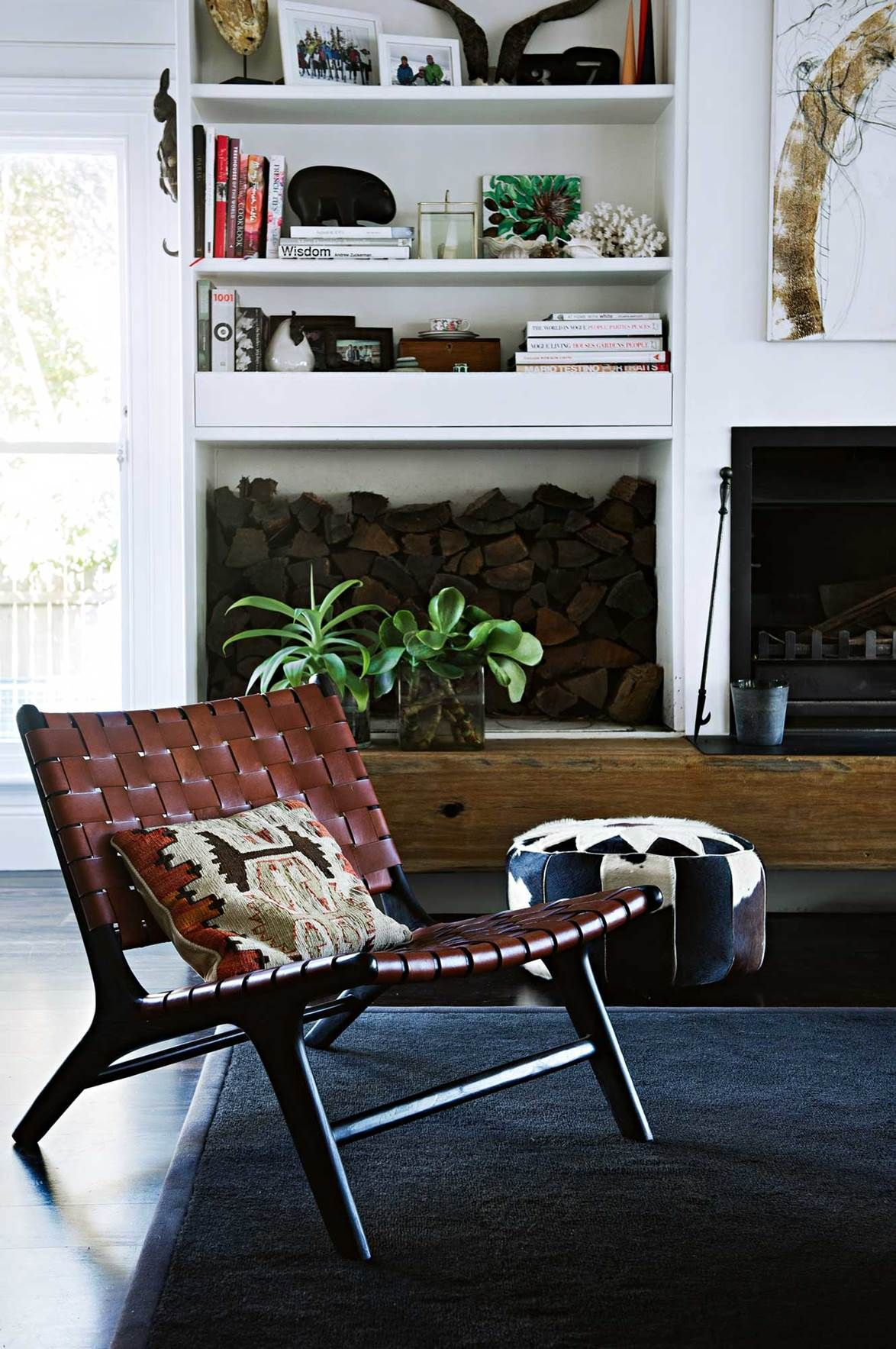 In the living room a solid timber shelf provides a hearth for the fireplace as well as storage for wood logs a woven chair is a nod to mid century modern