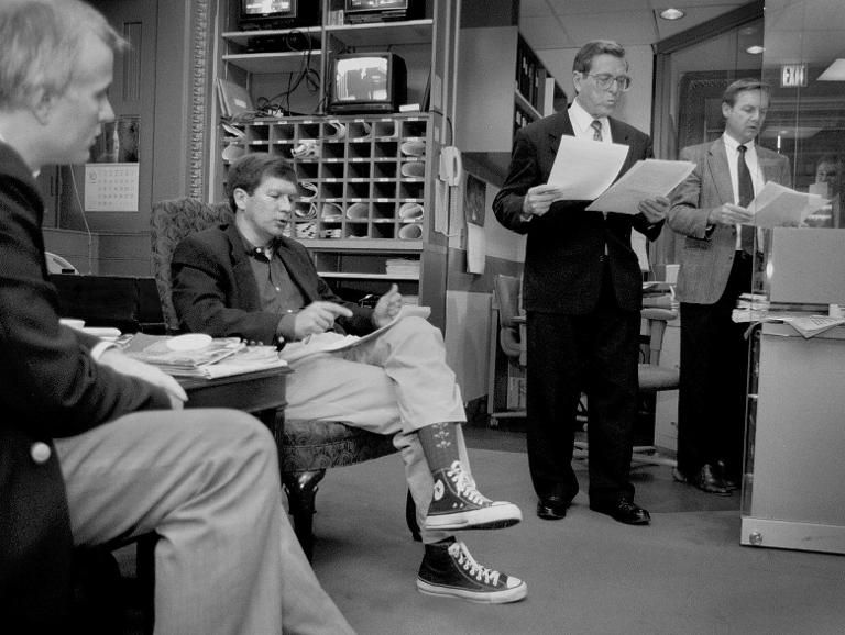 Rep. John R. Kasich (R-OH), seated 2nd from left, and Sen. Pete V. Domenici (R-NM) in the dark suit standing, go over their response to President Clinton's radio address just prior to recording the radio broadcast in the Senate studio on November 3, 1995. Kasich was casually dressed as the House was out of session for the weekend. (Photo: Robert A. Reeder/The Washington Post/Getty)