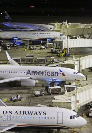 An American flight arrives at US Airways gate B6 during