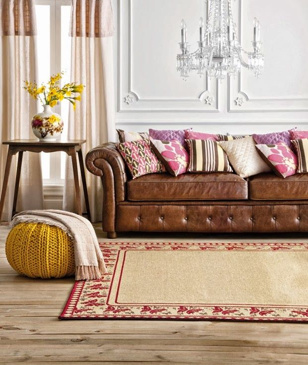 Tan leather Chesterfield sofa with pink and brown cushions, yellow knitted pouf, red and cream