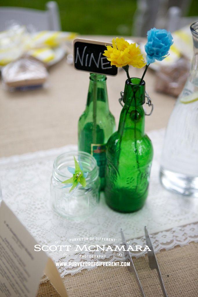 Green bottles make a simple statement on wedding tables.  www.purveyorofdifferent.com