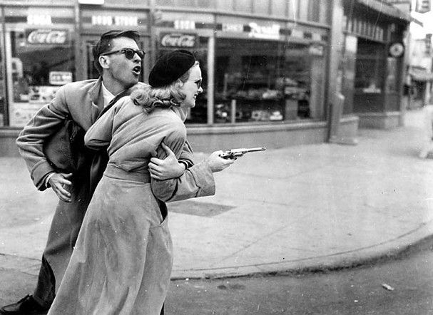 Gun Crazy (1950) Laurie (Peggy Cummins) tries to fire her revolver as she and Bart (John Dall) get away from a robbery. A famous photo still from the movie.