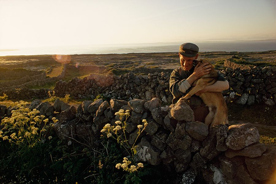 A farmer embraces his dog in his stonewalled field on