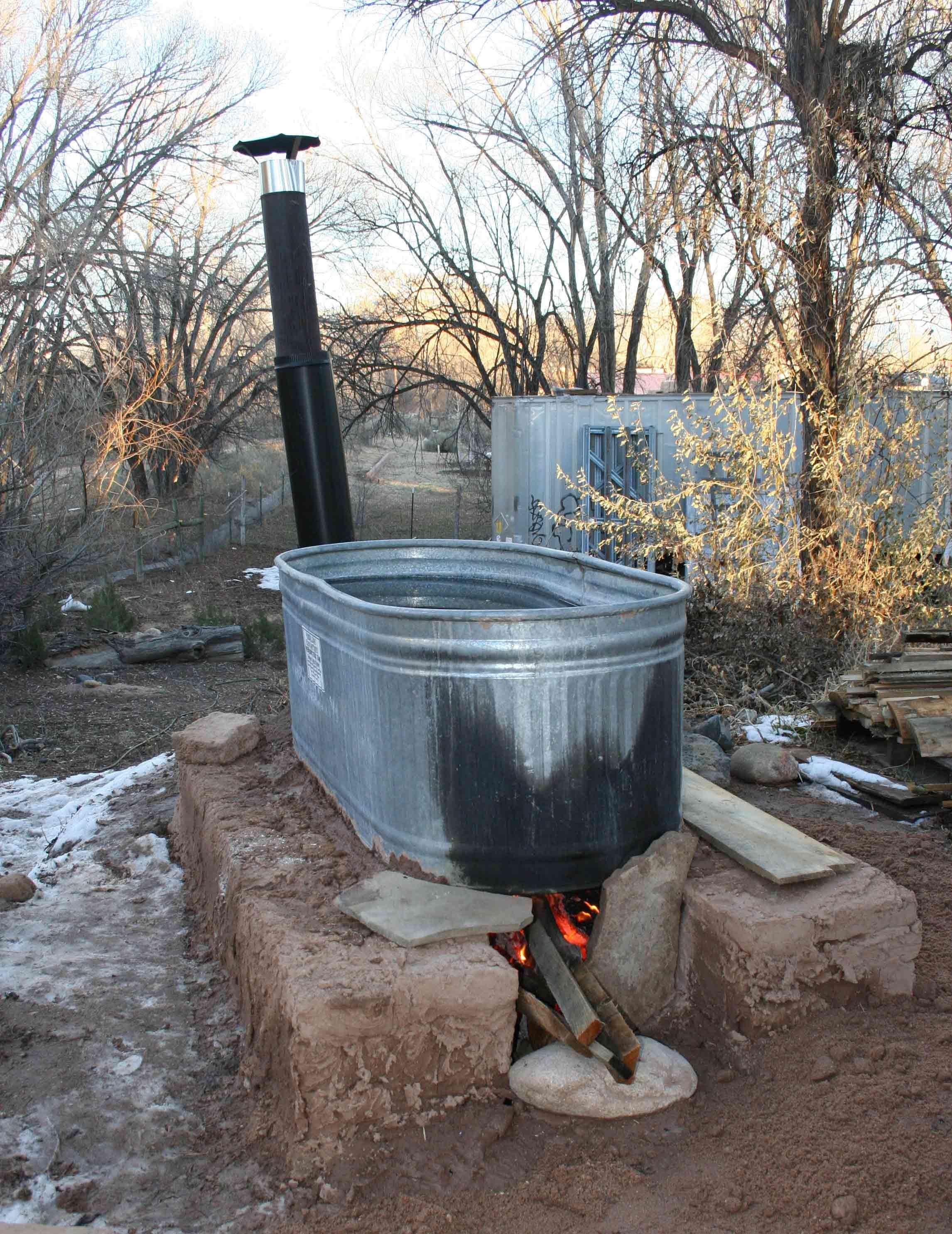 wood fired stock tank hot tub on 1/4 size adobe block base