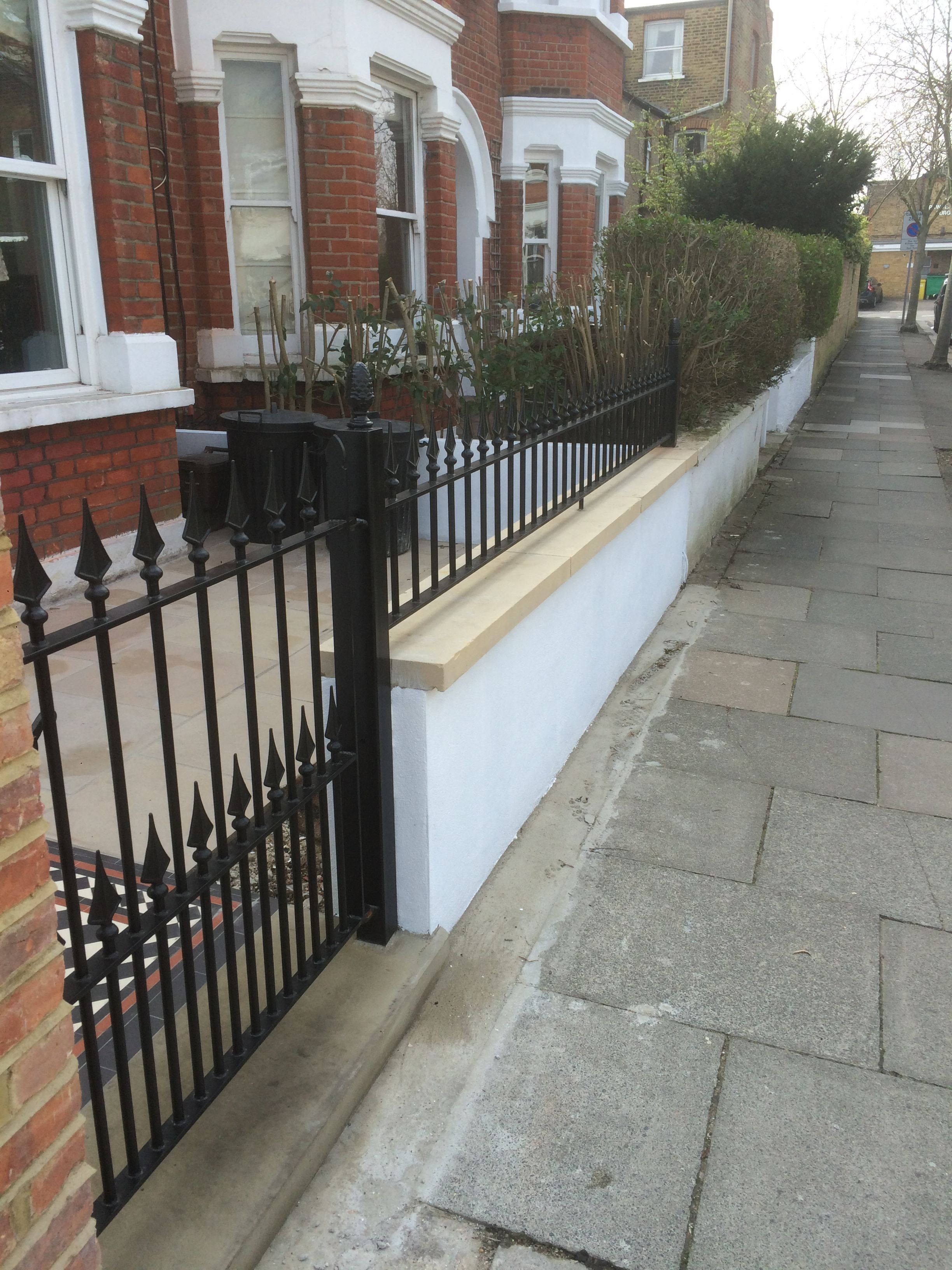Black cast iron gate and railings in London front garden