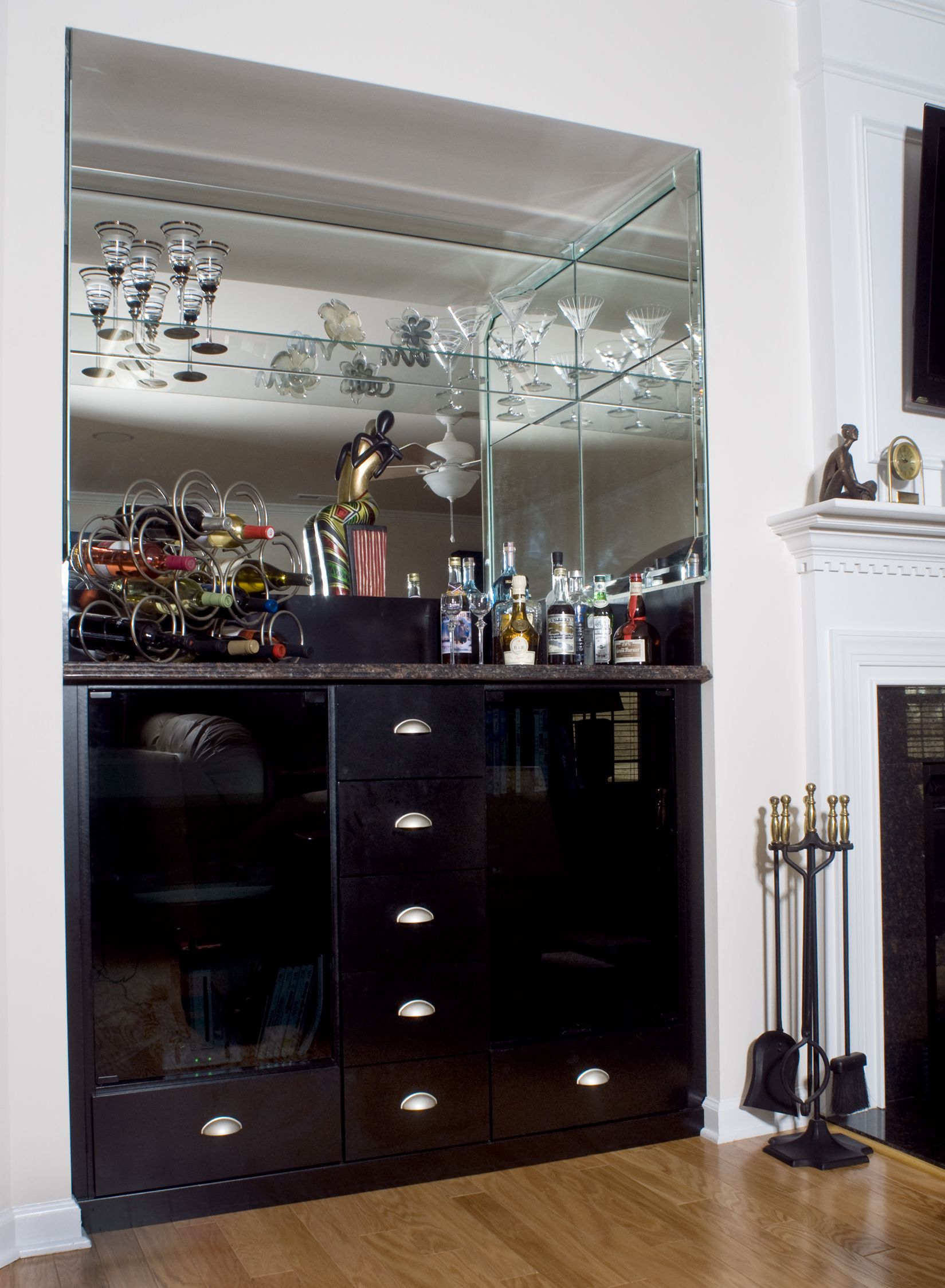 This actually custom wine bar fits perfectly into an empty wall indent and has been outfitted with glass backing and shelves. Perfect addition for those who hold living room gatherings at home.  #winebar #bar  Learn more: https://www.closetfactory.com/pantry-wine-cellars/
