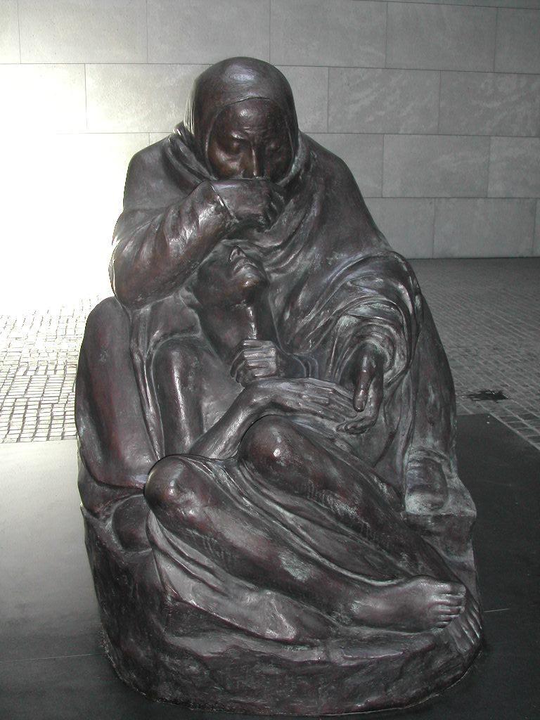 """Edificio de la Nueva Guardia de Berlín (Neue Wache) escultura de Käthe Kollwitz """"Madre con hijo muerto"""" ocupa el centro de la sala. Situada bajo el óculo, la escultura se expone a la nieve, la lluvia y el frío, que simboliza el sufrimiento de los civiles durante la Segunda Guerra Mundial."""