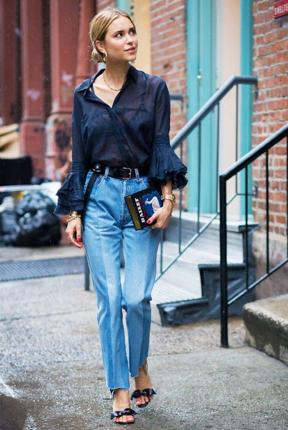Pernille Teisbaek wears a sheer blue blouse with ruffle sleeves, paneled jeans, sandals with bow-detailing, and an Olympia le Tan book clutch