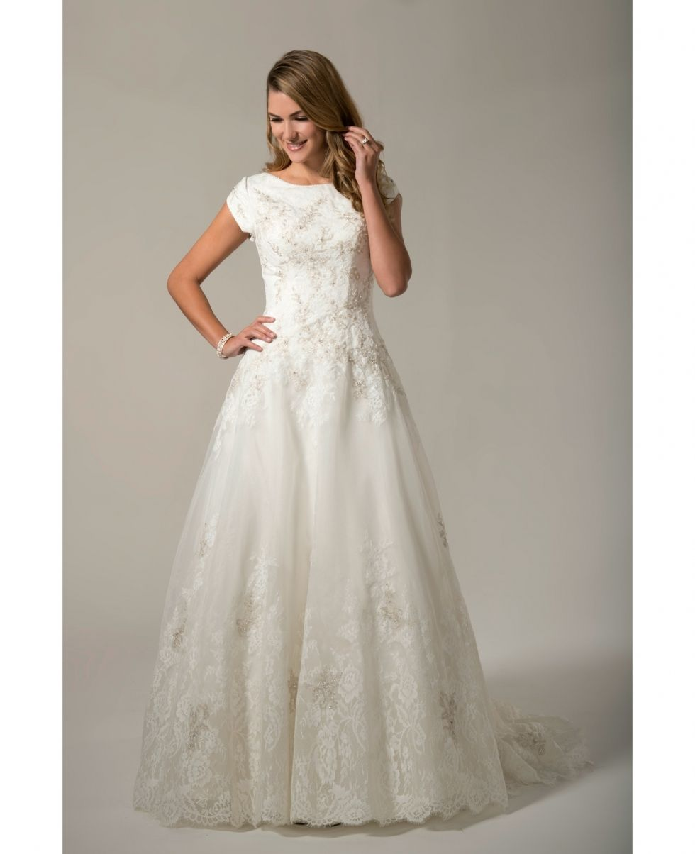3c30ecee9c1b Organza A-line gown with Tulip sleeves, scoop neckline finished with a  beaded trim. Bodice is embellished with beaded lace. Zipper back with  buttons.