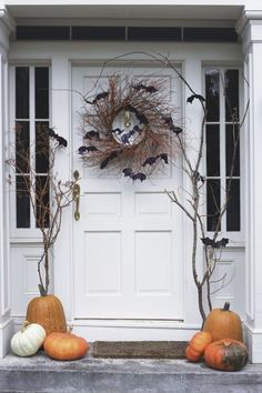 Halloween decor doesn't have to be scary. Have a chic look with white pumpkins and a batty wreath.