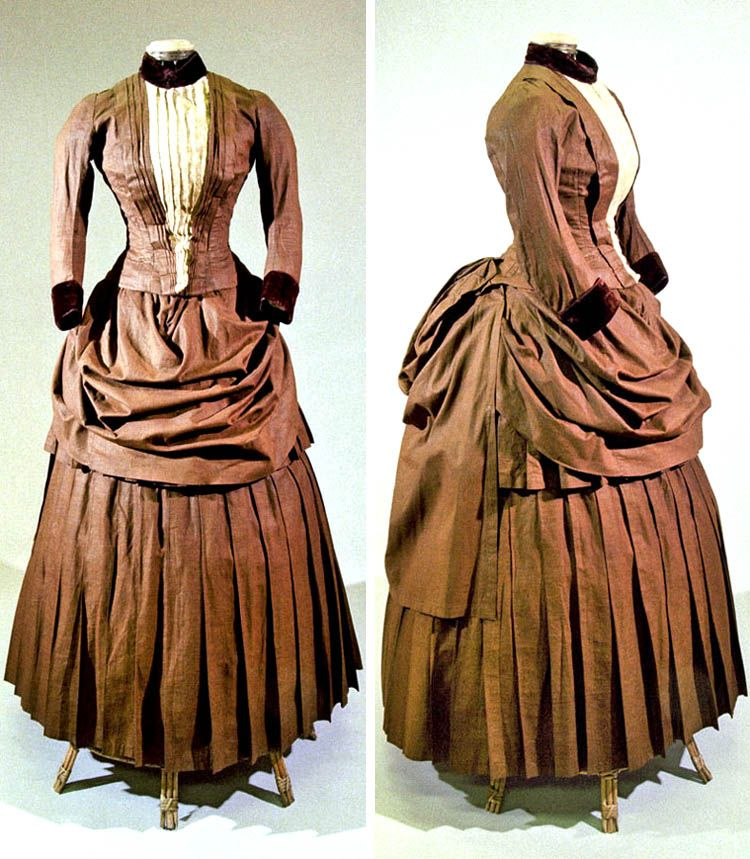 Walking dress, Bohemia, circa 1885. Brown cotton canvas with brown velvet trim, machine-sewn. Boned, fitted, and lined bodice with lace inset, standup collar, and 11 hidden pearl buttons. Bustle skirt lined in oilcloth. Via North Bohemian Museum.