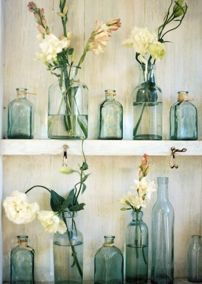 Using repurposed bottles create vases filled with flowers for decor