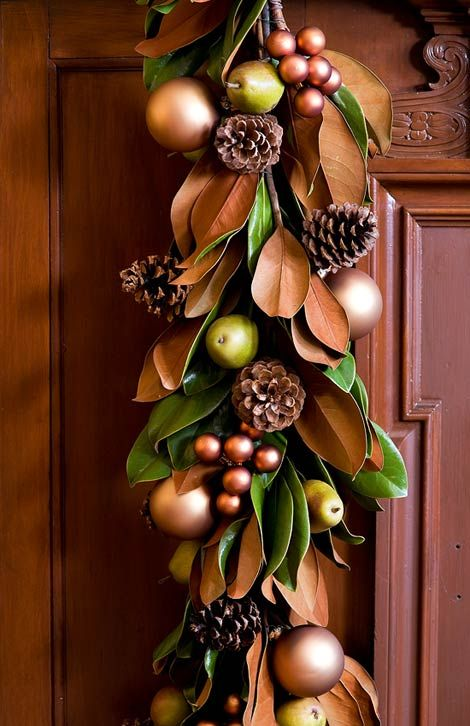 Festive Holiday Staircases and Entryways | Magnolia leaves, pears, and copper-colored glass balls create a masculine garland for a wooden door. The ornaments' diffused sheen makes the arrangement glow, while pinecones add texture. | Home®