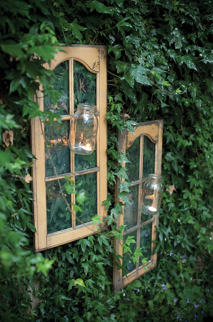 Old hutch doors removed and hung on the fence. Add a mason jar and tea light for subtle lighting. Great addition to your home's backyard