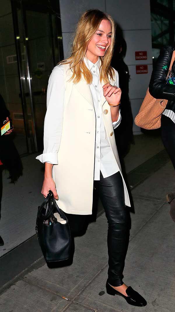 Margot Robbie usa camisa branca, colete off white, calça de couro e mocassim