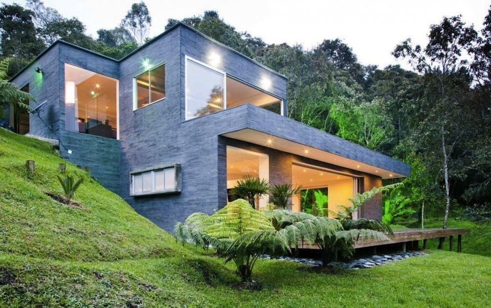 Hillside House With Stone Wall And Glass Windows And Door With All