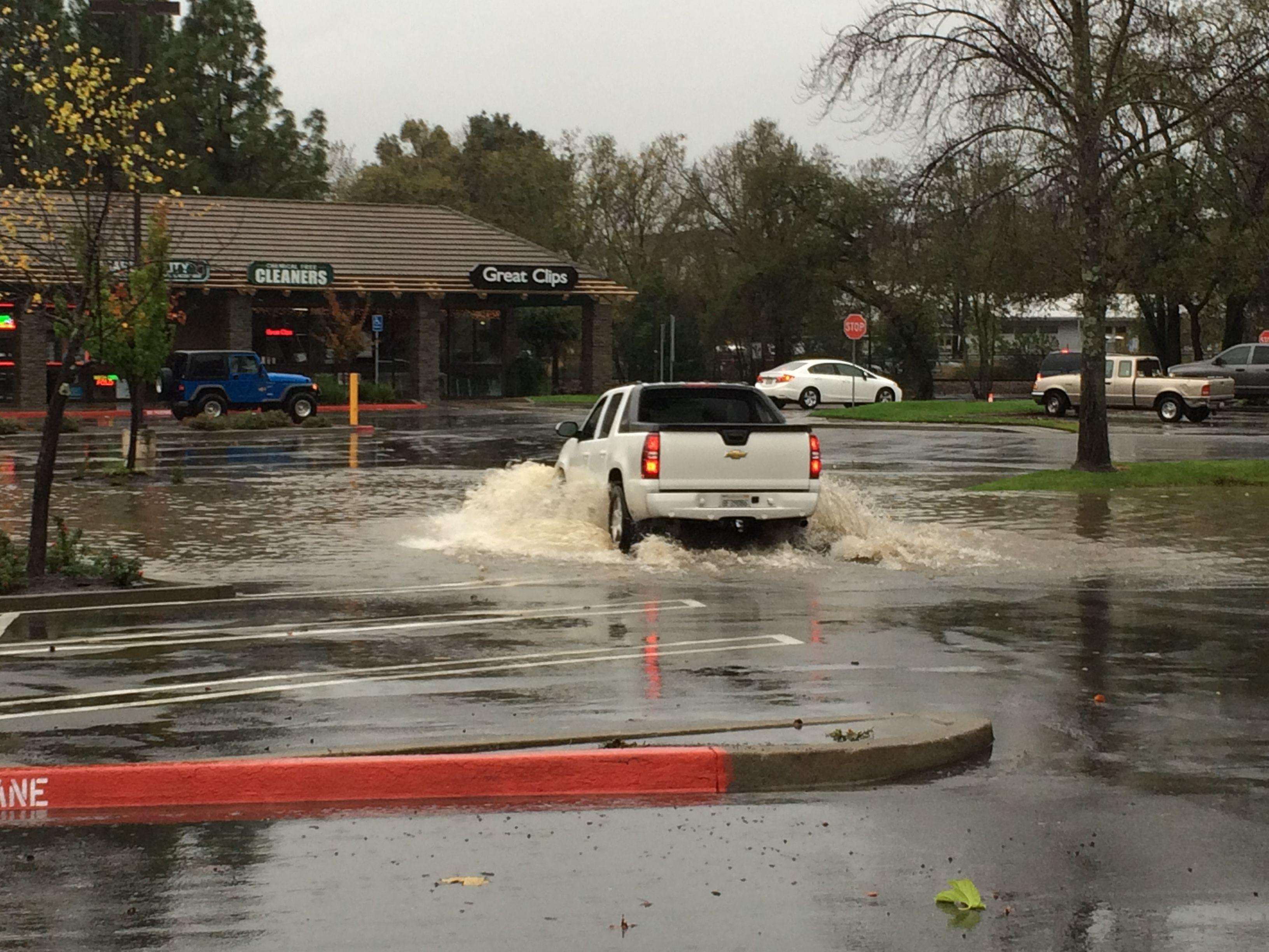 Truck runs through deep water in flooded parking lot