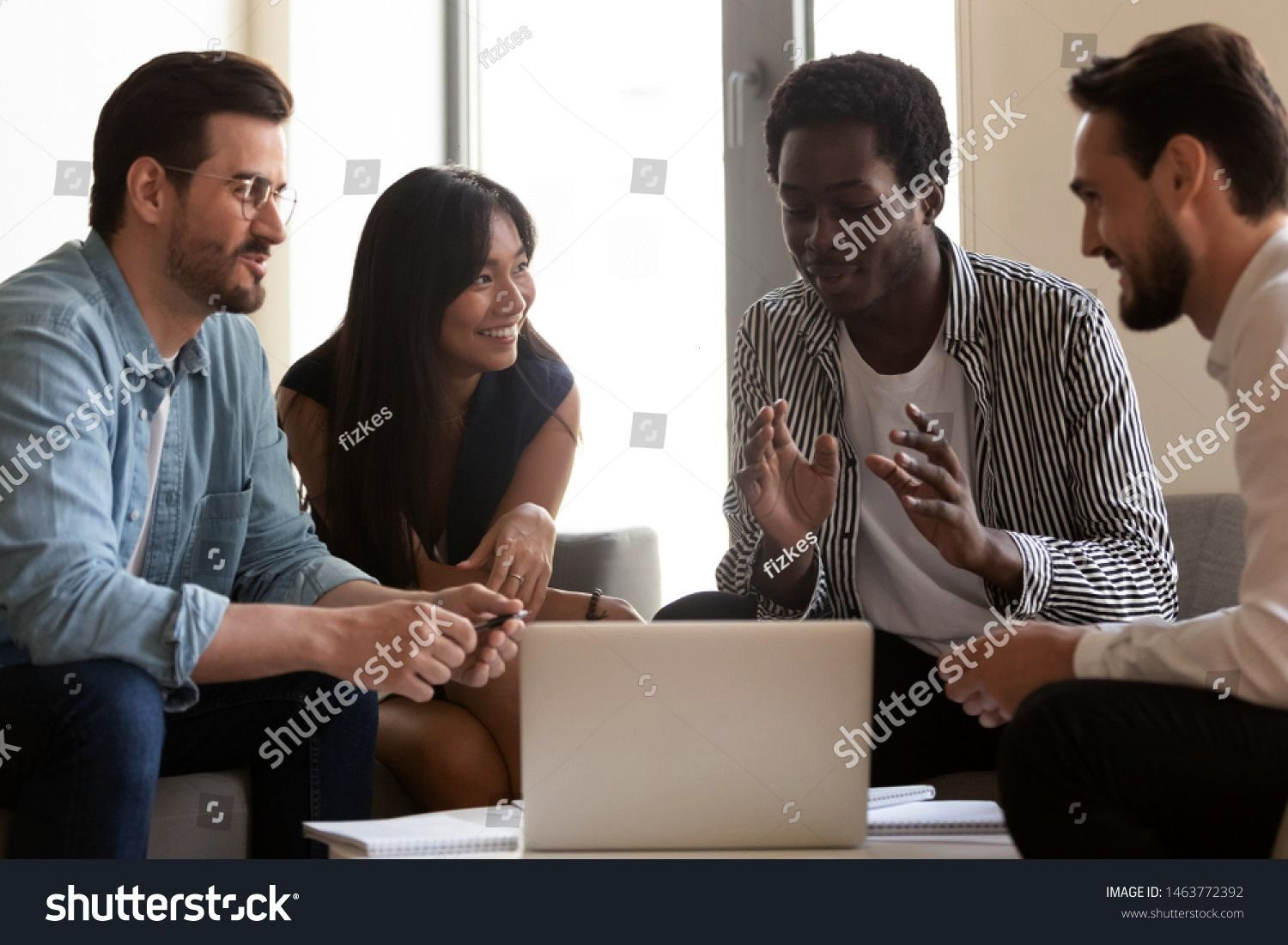business team listen to african leader mentor coach explain online strategy with laptop diverse workers group brainstorm talking gathered in office work together at teamw...