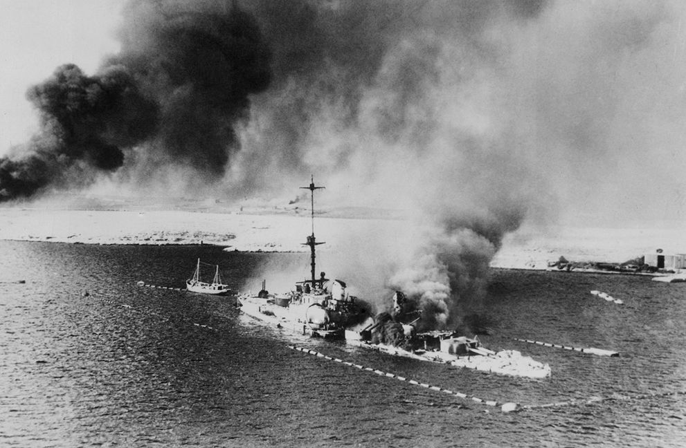 10 This photo, made from a British warplane during the assault of Tobruk shows the Italian Cruiser San Giorgio, burning amidships, in the harbor of Tobruk, on February 18, 1941. The ship was scuttled, its decks appear to be covered with wrecked and smashed gear. (AP Photo) #