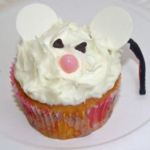 """Mouse cupcake... pretty easy looking, and cute!  Make the """"fur"""" by pulling up the frosting with a knife or toothpick to form little peaks.  Just add a pink M&M for nose, chocolate chip eyes, white chocolate wafers for ears, and even a black licorice string for the tail.  I would add a cute little smiling mouth with another piece of licorice.  :) option for #missmouse birthday cakes??"""