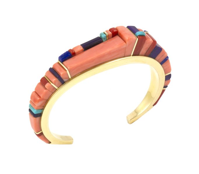 An absolute stunning 18k gold Mediterranean coral bracelet by Charles Loloma.  Inlayed with accents of lapis, sugilite, and Lone Mountain turquoise.  Measures 5″ with a 1 1/4″ opening.  1/2″ width.  9/16″ height at highest point.