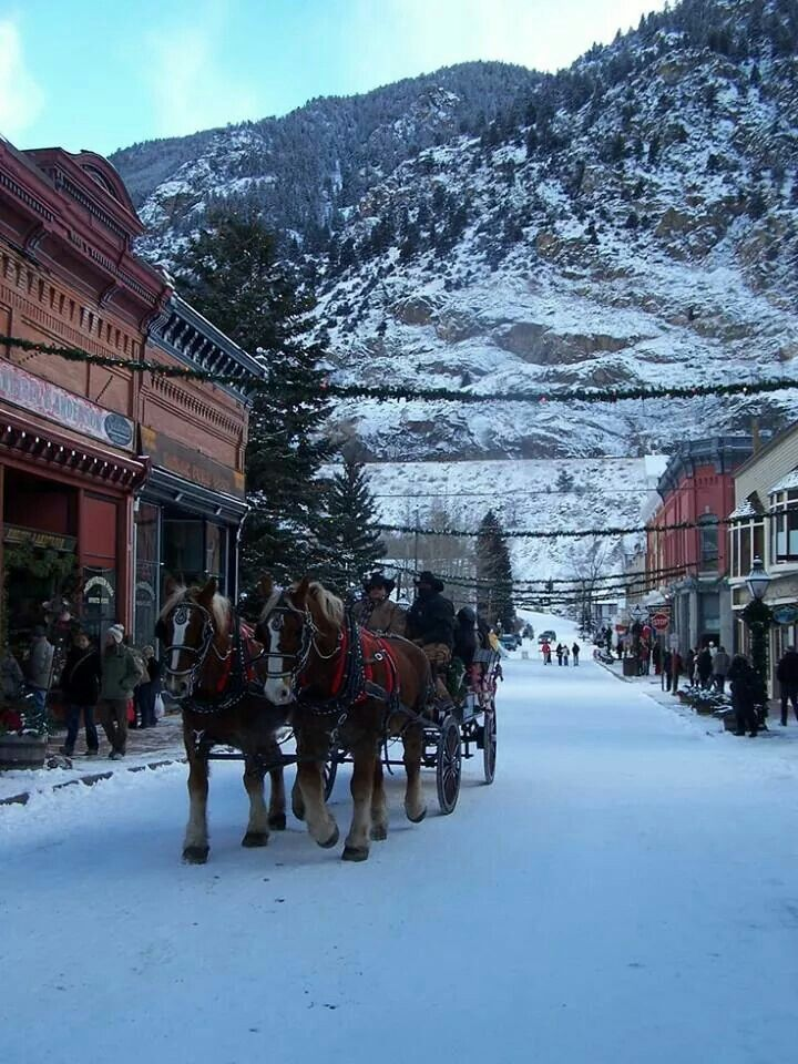 Christmas In Colorado Mountains.A Horse Drawn Carriage In A Snow Covered Mountain Village At