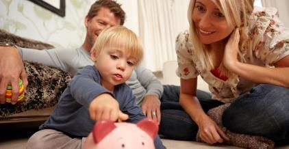 Parents watch son put coins in piggy bank © Image Source/Getty Images