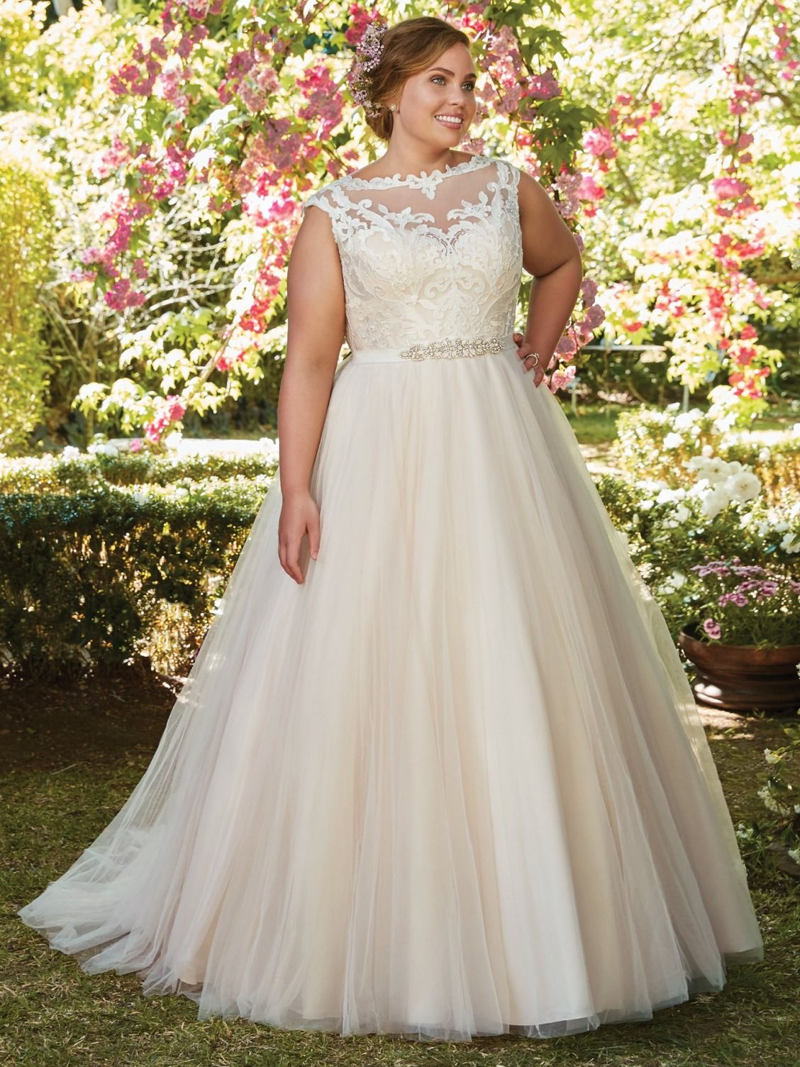 CARRIE - Rebecca Ingram. Charming and romantic, this tulle ballgown features lace appliqués that cascade over the bodice, illusion bateau neckline, and illusion back. Finished with covered buttons and zipper closure. Detachable beaded belt on grosgrain ribbon sold separately.