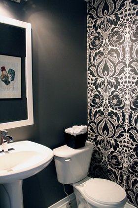 O banho com revestimento preto poderia ter o restante das paredes com papel de parede à prova dágua.