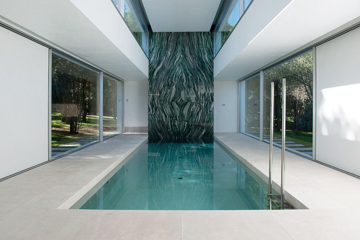 Espectacular alberca interior, en medio de la casa, resalta por la iluminación lateral, así como por el granito de remate.