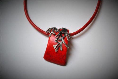 Karmen Jeden z mála červených šperků, které jsem vytvořila. Jeho základem je speciálně upravená a barvená hovězí kost, takže přírodní materiál. Kost je mírně prohnutá, ozdobena je cínovanými větvičkami, které jsem napatinovala, naleštila a ošetřila proti oxidaci. Nyný už jen stačí pravidelně je naleštit vatičkou na ošetření stříbra. Přívěšek je zavěšen na silné, červené, kulaté kůži. Není zcela souměrný, tvar kosti jej malinko vychyluje z osy.