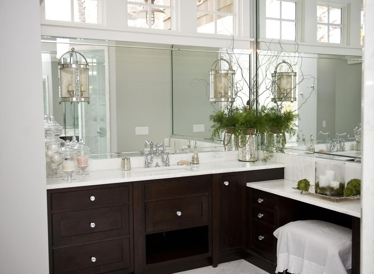 va luxurious bathroom with dark cabinets and white countertops
