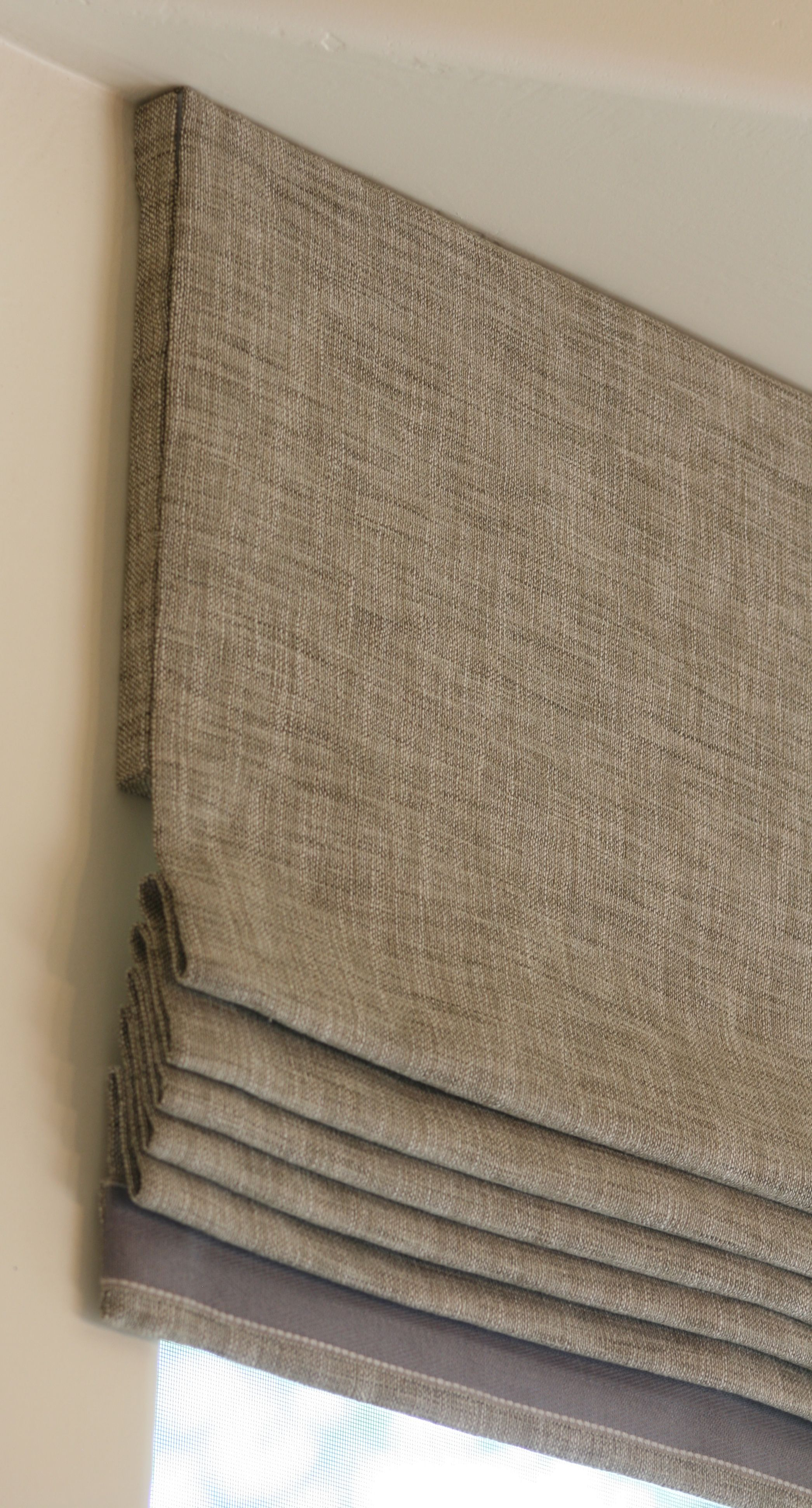 Neat edge and trim to Roman blind could take this up to ceiling for