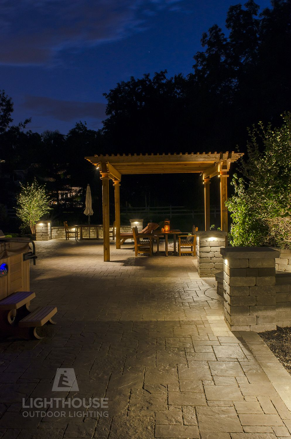 Low Voltage Lighting Set In The Walls And Pergola Of This Backyard Create An Inviting