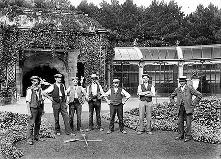This country house was built 1874-83 for Baron Ferdinand de Rothschild in the style of a 16th-century French chateau. This group of gardeners has stopped work to have their photograph taken. Some of them seem less relaxed about this than others. The building behind the men is the aviary, built in 1889. Photographer:S W A NewtonDate Taken:1905