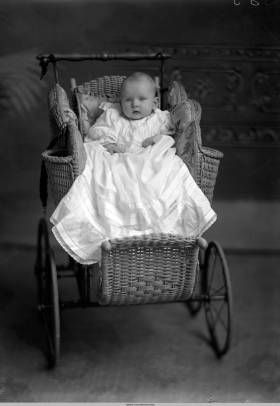 A baby in white christening gown is sitting in a wicker stroller :: W. R. Gray Studio Photographs