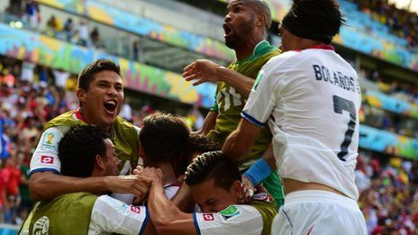 Costa Rica's players celebrate after their team scored against Italy