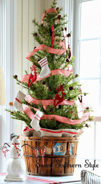Savvy Southern Style:tabletop Christmas tree decorated with vintage grain sack stockings and placed in a vintage orchard basket.