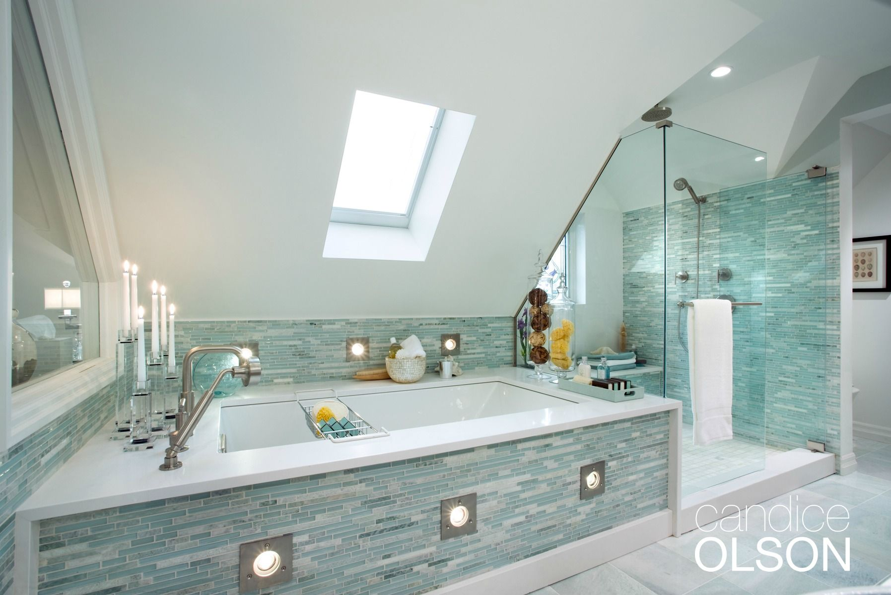 A deep soaker tub with a broad white quartz deck invites hours of ...